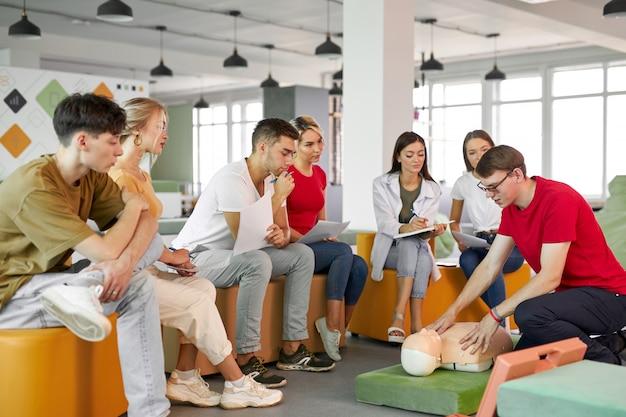 Clase de reanimación cardiopulmonar con instructores jóvenes caucásicos hablando y demostrando ayuda de primeros auxilios