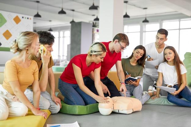 Clase de reanimación cardiopulmonar con instructores jóvenes que demuestran ayuda en primeros auxilios