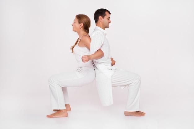 Clase de yoga combinada con el entrenador. hombre y mujer haciendo el ejercicio.