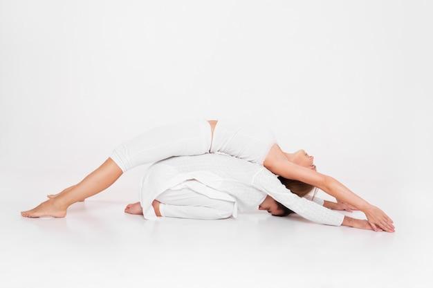 Clase de yoga combinada con el entrenador, la mujer y el hombre haciendo estiramientos