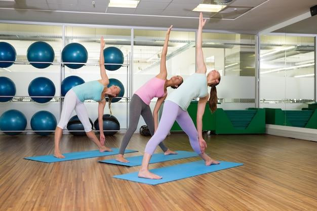 Clase de yoga en posición de trailing extendida en gimnasio