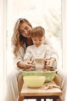 Clases de alfarería. joven madre caucásica enseñando a su hijo. hijo haciendo olla de barro en torno de alfarero.