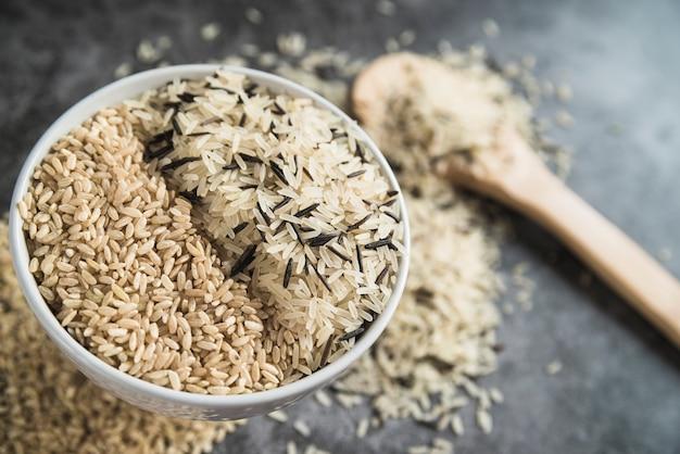 Clases de arroz en un tazón cerca de una cuchara de madera