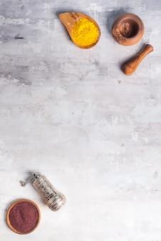 Clases de especias de diferentes moler en un tazón de madera con un molinillo en piedra, endecha plana
