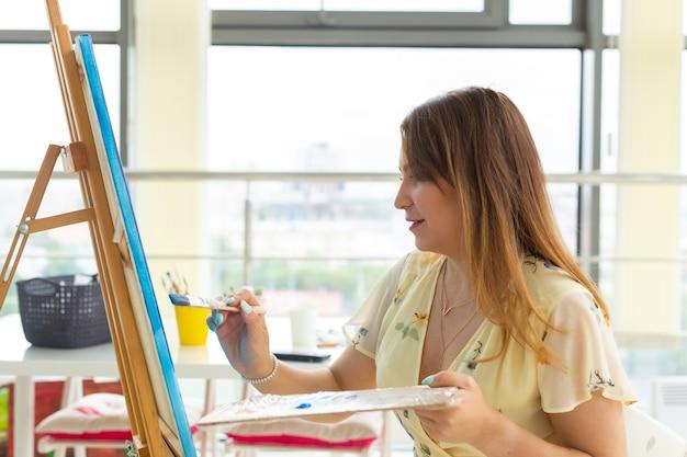 Clases de pintura. cursos de dibujo. habilidades de imaginación e inspiración. muchacha encantadora del estudiante que crea el cuadro en el caballete.