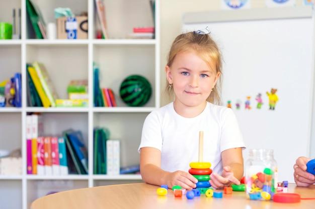 Clases de terapia del desarrollo y del habla con una niña. ejercicios y juegos de logopedia con una pirámide de colores