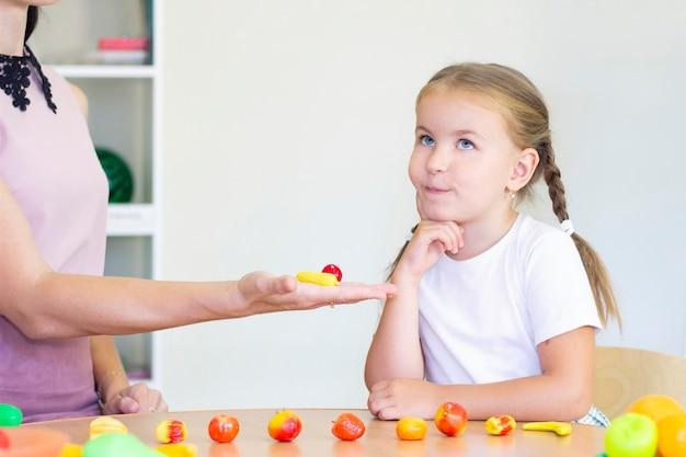 Clases de terapia del desarrollo y del habla con una niña. ejercicios de logopedia y juegos de contar. la chica pensó