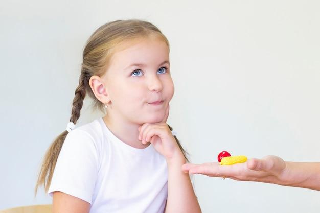 Clases de terapia del desarrollo y del habla con una niña. ejercicios de logopedia y juegos de conteo. la chica pensó