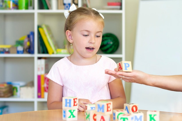 Clases de terapia del desarrollo y del habla con una niña. ejercicios de logopedia y juegos con letras.