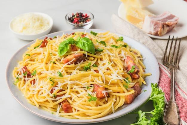 Clásica pasta italiana casera carbonara con tocino, huevos, queso parmesano y perejil en un plato con tenedor