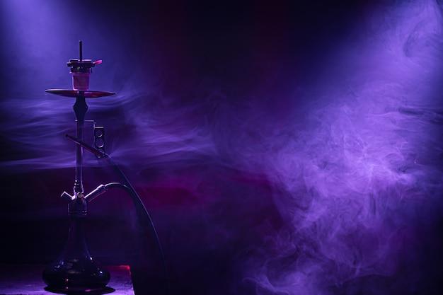 La clásica pipa de agua. hermosos rayos de luz y humo de colores. el concepto de fumar pipa de agua.