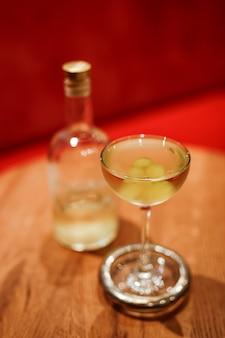 Un clásico cóctel de martini seco en una elegante copa cupé, adornado con uvas.