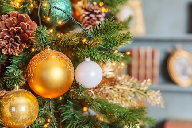 Clásico navidad año nuevo decorado árbol de año nuevo con adornos de oro decoraciones juguete y bola.
