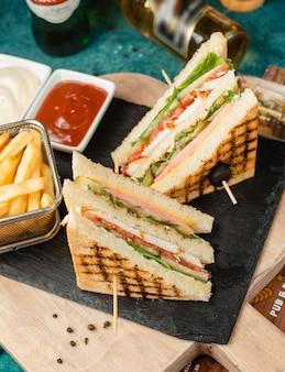 Clásico sándwich club con papas fritas y salsa