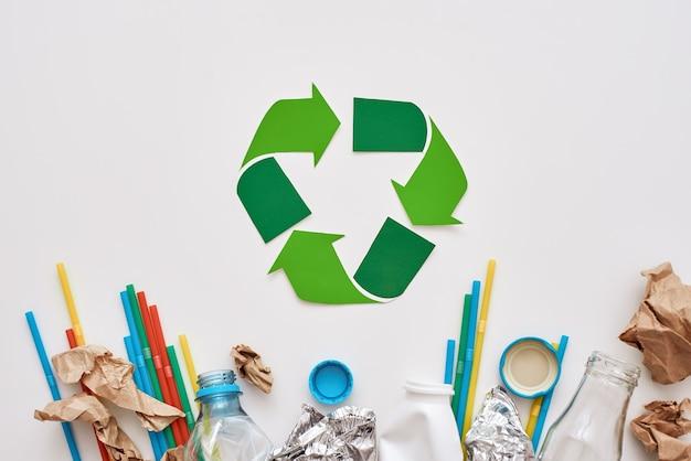 Clasifica tu basura. lámina arrugada, papel y plástico se encuentran debajo del símbolo de reciclaje. diferentes tipos de basura sin clasificar.