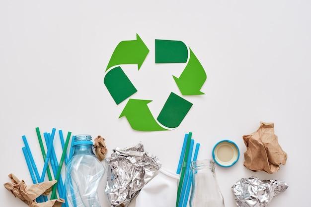 La clasificación de basura salva al mundo. lámina arrugada, papel y plástico se encuentran debajo del símbolo de reciclaje. diferentes tipos de basura sin clasificar.