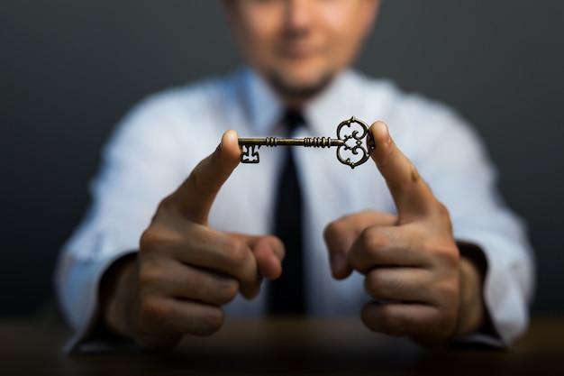 Clave para el éxito en la mano del hombre de negocios en el fondo del cielo.