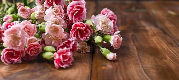 Clavel con pétalos de rosas y blancos sobre una mesa de madera. un ramo de flores como regalo. foto de época espacio libre para texto.
