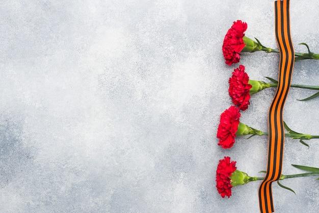 Claveles rojos y cinta de san jorge en un fondo concreto.
