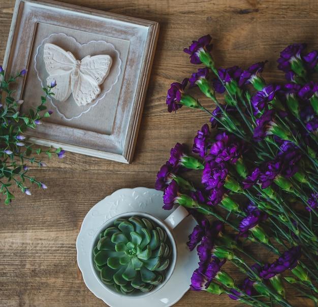 Claveles violetas, suculentos y marco con mariposa