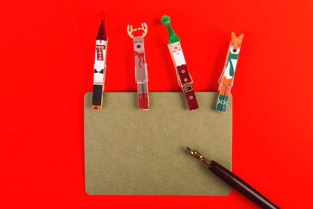 Clavijas de ropa decoradas para navidad con cartel y pluma.
