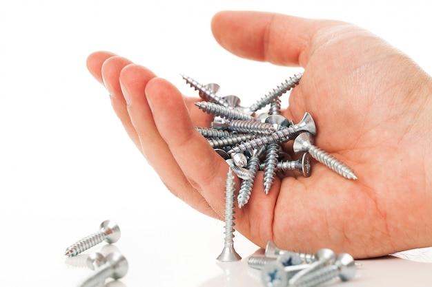 Clavos plateados en mano humana