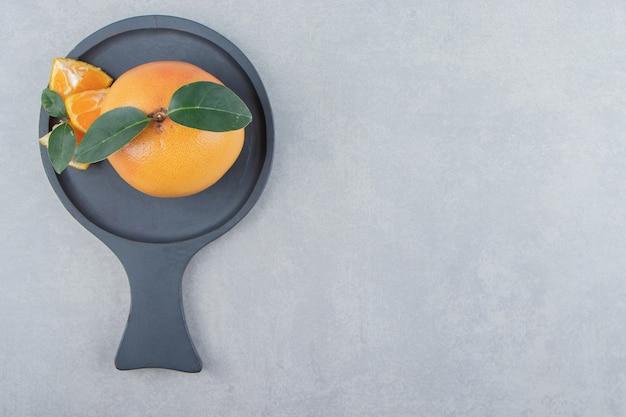 Clementina fresca y segmentos sobre tabla de cortar negra