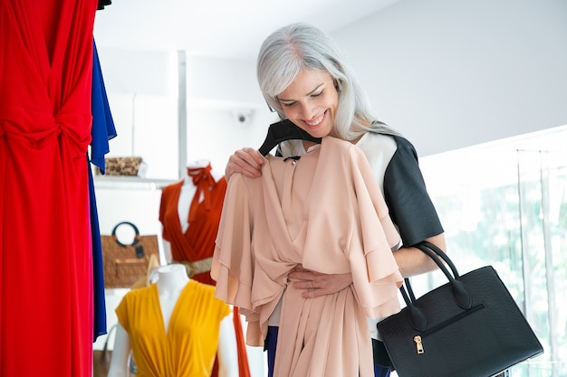 Clienta alegre disfrutando de las compras, aplicando vestido con percha. mujer eligiendo ropa en tienda de moda. concepto comercial o minorista