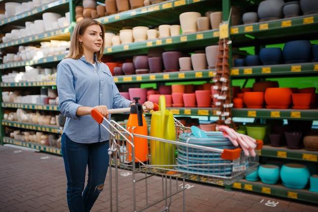 Clienta con carrito comprando herramientas para jardinería. mujer elegir equipos en tienda para floricultura, compra de instrumentos de floristería