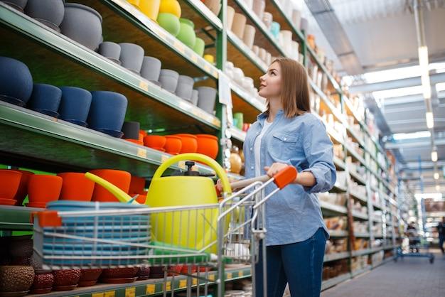 Clienta con carrito comprando herramientas para jardinería. mujer eligiendo equipos en tienda para floricultura