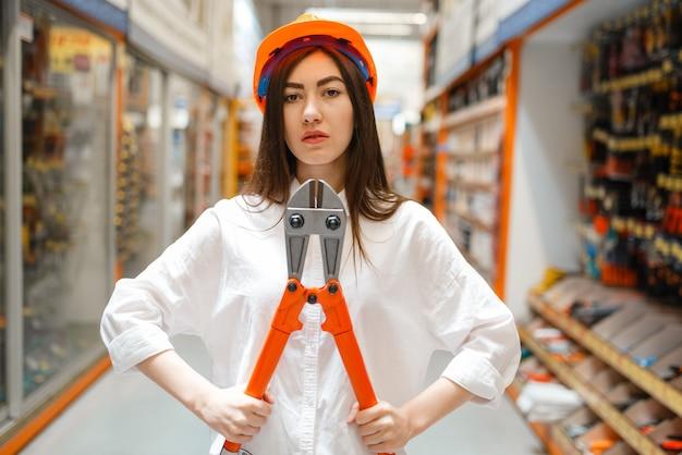 Clienta en casco eligiendo cortadores de alambre metálico en ferretería. el comprador mira las mercancías en la tienda de bricolaje, compras en el supermercado del edificio