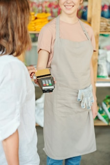 Clienta contemporánea con tarjeta de crédito a través de terminal de pago en manos de joven dependienta sonriente de supermercado de jardinería