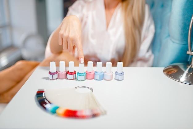 Clienta elegir esmalte de uñas en salón de belleza.
