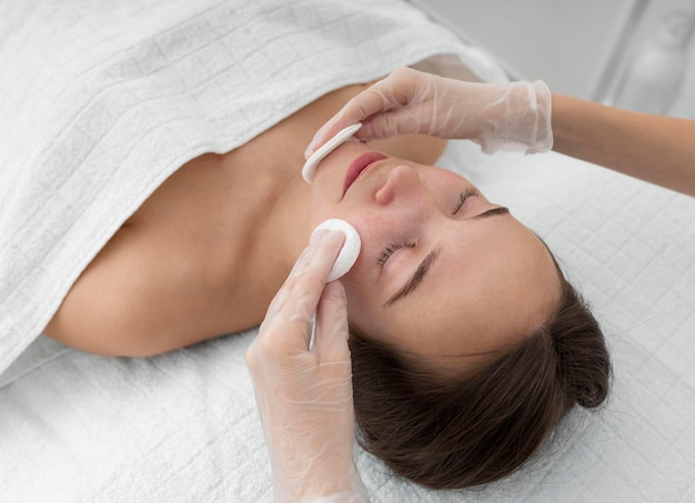 Clienta en el salón de rutina de cuidado facial con discos de limpieza