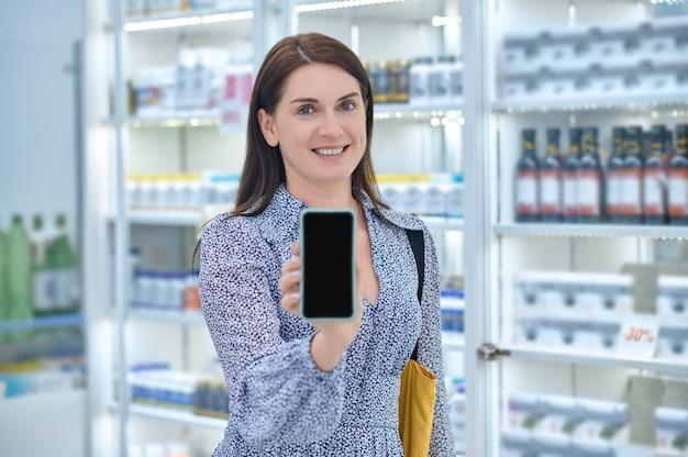 Clienta sonriente con el teléfono móvil de pie en la farmacia