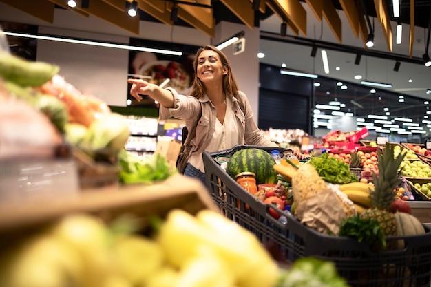 Clienta en el supermercado señalando con el dedo a los estantes de frutas en la tienda de comestibles.
