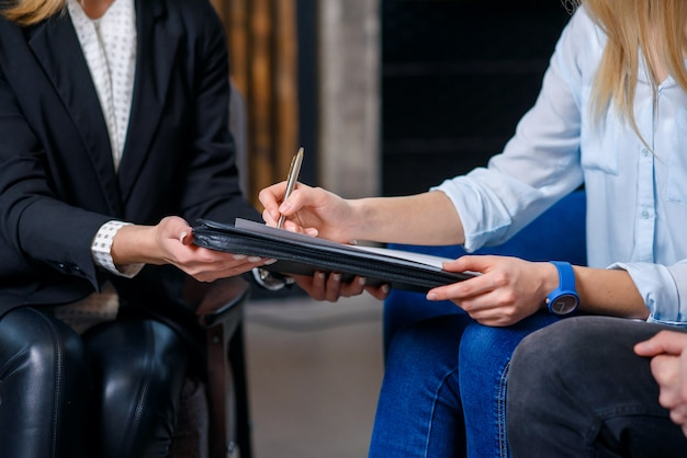 Las clientas firman un contrato para comprar una casa nueva, plana.