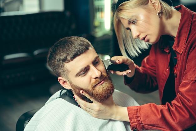 Cliente durante el afeitado de barba en peluquería. peluquería femenina en el salón. igualdad de género. mujer en la profesión masculina.