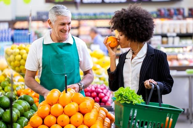 Cliente africano con verdulero, sosteniendo fruta naranja.