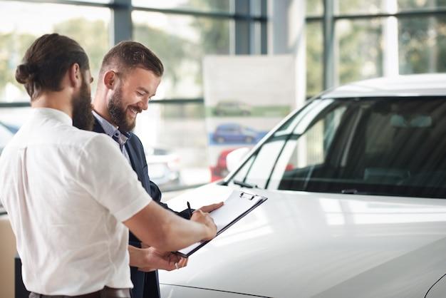 Cliente de auto firmando documentos de compra en carpeta.