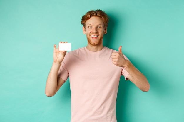 Cliente de banco masculino alegre en camiseta mostrando el pulgar hacia arriba y tarjeta de crédito plástica, sonriendo satisfecho a la cámara, de pie sobre fondo turquesa.