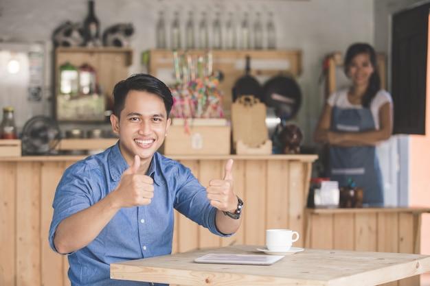 Cliente de café satisfecho mostrando el pulgar hacia arriba