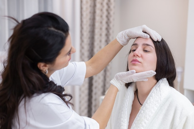 Un cliente en una cita con un esteticista, consulta, modelado de la cara, preparación para los próximos procedimientos, examen visual de las áreas problemáticas.