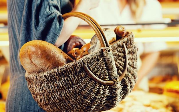 Cliente compra pan en panadero llevando cesta