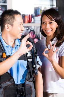 Cliente comprando equipo en tienda de buzos