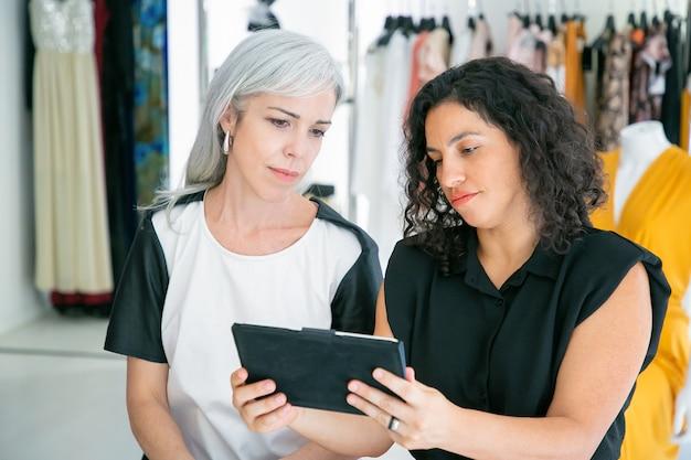 Cliente concentrado y asistente de tienda reuniéndose en una tienda de moda, sentados juntos y usando la tableta, discutiendo sobre ropa y compras. consumismo o concepto de compras
