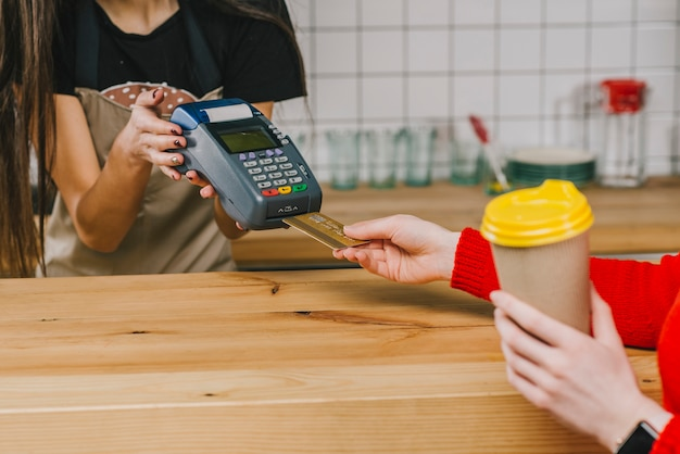 Cliente de cultivo que paga por una bebida en el café