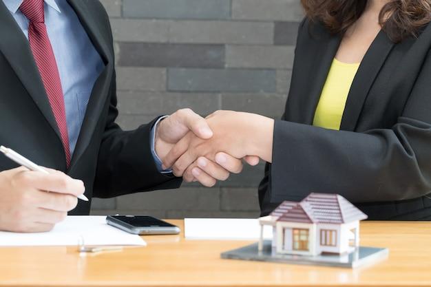 El cliente se da la mano y acuerda con un agente de bienes raíces en la oficina