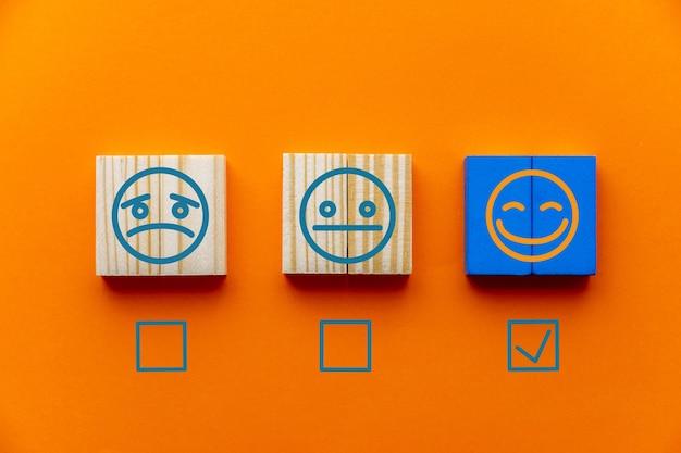 El cliente eligió el emblema de la cara feliz en un cubo de madera con fondo naranja, así como las nociones de evaluación de servicio al cliente y encuesta de satisfacción.
