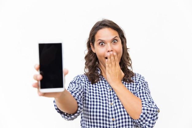 Cliente emocionado sorprendido que muestra la pantalla del teléfono en blanco